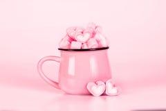 Forme de coeur de guimauve dans la tasse sur le fond rose avec amour concentré Photographie stock