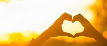 Forme de coeur de main de silhouette avec la lumière du soleil Photographie stock