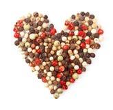 Forme de coeur de poivre de couleur d'épices sur le blanc Photographie stock