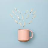 Forme de coeur de rangée de feuille et tasse de café en pastel Images stock
