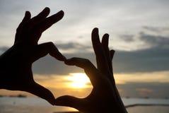 Forme de coeur de silhouette des mains humaines Photographie stock