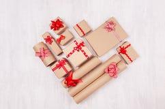 Forme de coeur des cadeaux de Noël des cadeaux de papier de métier avec les rubans rouges et des arcs sur le panneau en bois blan image libre de droits