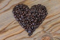 Forme de coeur des grains de café sur le vieux fond en bois Image stock