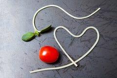 Forme de coeur des tomates de spaghetti et de raisin sur la casserole noire Images libres de droits