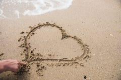 Forme de coeur de dessin de main sur le sable Images stock