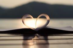 Forme de coeur du livre de papier au coucher du soleil avec la réflexion de la lumière sur une surface de l'eau (fond de vintage) Images stock