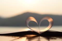 Forme de coeur du livre de papier au coucher du soleil avec la réflexion de la lumière sur une surface de l'eau (fond de vintage) Images libres de droits