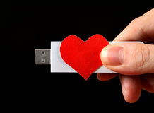 Forme de coeur et commande d'USB dans la main Photographie stock