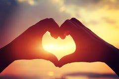 Forme de coeur faisant des mains contre le coucher du soleil lumineux de mer Images libres de droits