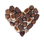 Forme de coeur faite à partir de divers bonbons de chocolat d'isolement sur le blanc Photos stock