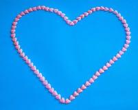 Forme de coeur faite à partir de petits coeurs roses de sucrerie Images stock