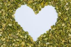 Forme de coeur faite à partir des graines de citrouille épluchées Image stock