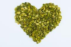 Forme de coeur faite à partir des graines de citrouille épluchées Images libres de droits