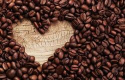 Forme de coeur faite à partir des grains de café sur la surface en bois Image stock