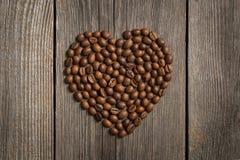 Forme de coeur faite à partir des grains de café sur la table en bois image libre de droits
