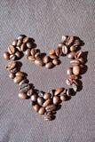Forme de coeur faite à partir des grains de café sur le fond brun Image libre de droits