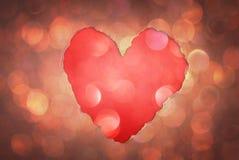 Forme de coeur faite à partir du papier déchiré au-dessus des lumières molles de boke de scintillement. Image libre de droits