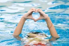 Forme de coeur faite de belle main monter à partir de l'eau Photographie stock libre de droits