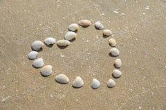 Forme de coeur faite de coquilles sur la plage sablonneuse Photographie stock