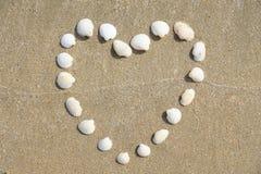 Forme de coeur faite de coquilles sur la plage sablonneuse Photo libre de droits