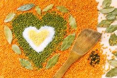 Forme de coeur faite de grains jaunes mélangés de blé, sel blanc, vert Images stock