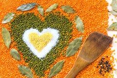 Forme de coeur faite de grains mélangés de blé, sel, fèves de mung vertes, Images stock