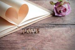 Forme de coeur faite de pages avec la fleur sur le vieux bois Photos stock