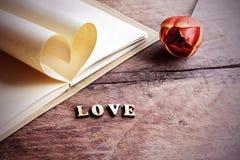 Forme de coeur faite de pages avec la fleur sur le vieux bois Photo stock