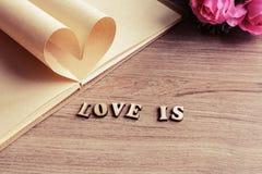 Forme de coeur faite de pages avec la fleur sur le vieux bois Image libre de droits