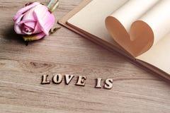 Forme de coeur faite de pages avec la fleur sur le vieux bois Images stock