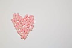 Forme de coeur faite de pilules roses de capsule d'isolement sur le backgro blanc Photographie stock libre de droits