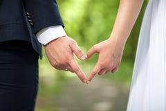 Forme de coeur faite de mains femelles et mâles ensemble les amants couplent faire un coeur avec des mains sur le fond vert Photos stock