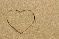 Forme de coeur gravée dans une plage sablonneuse humide Photographie stock libre de droits