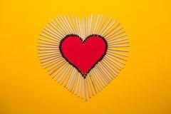 Forme de coeur de l'amour des matchs sur un fond jaune Photographie stock libre de droits