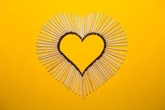 Forme de coeur de l'amour des matchs sur un fond jaune Photographie stock