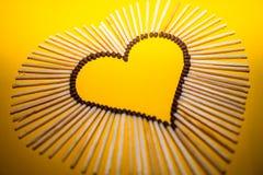 Forme de coeur de l'amour des matchs sur un fond jaune Images stock