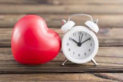Forme de coeur, réveil sur un fond en bois Image libre de droits