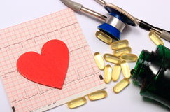 Forme de coeur sur le graphique et le stéthoscope d'électrocardiogramme avec des comprimés Photographie stock libre de droits
