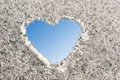 Forme de coeur sur une surface neigeuse, fond bleu Image libre de droits