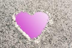 Forme de coeur sur une surface neigeuse, fond rose Photos stock
