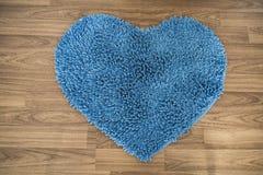 Forme de coeur, tapis de grattoir de pied sur le plancher en bois Photographie stock