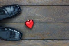 Forme de coeur de vue supérieure avec des chaussures du ` s des hommes sur le fond en bois avec Photo libre de droits