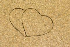 Forme de deux coeurs gravée dans une plage sablonneuse humide Photo libre de droits