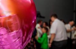 Forme de fête rose de ballons de coeur avec les invités de partie à l'arrière-plan Photo libre de droits
