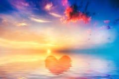 Forme de coeur dans l'océan calme au coucher du soleil. Beau ciel Photos stock