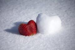 Forme de fraise et de coeur de neige sur le fond blanc de neige Image stock