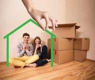 Forme de maison verte avec la jeune famille à l'intérieur Photos libres de droits