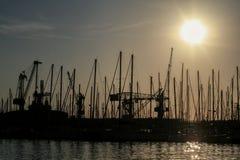 Forme des mâts et des grues de bateau au coucher du soleil dans le port de Toulon, France Photos stock