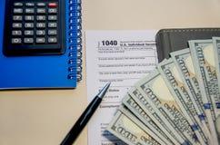 Forme 1040 di imposta, dollari, calcolatore, taccuini e una penna su una tavola di legno immagine stock