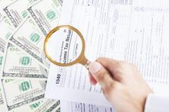 Forme di imposta e soldi del dollaro sotto la lente d'ingrandimento fotografia stock